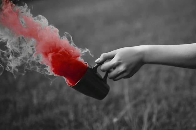 Mode foto van hand met kop en rode rook Gratis Foto