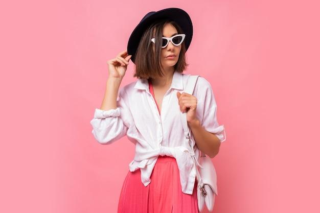 Mode foto van mooie brunette vrouw in lente outfit poseren stijlvolle zonnebril. Gratis Foto