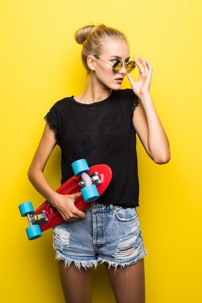 Mode gelukkig lachend hipster cool meisje in zonnebril en kleurrijke kleding met skateboard plezier buitenshuis tegen de oranje achtergrond Gratis Foto