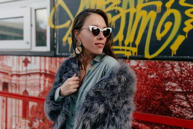 Mode glamour vrouw in trendy bontjas en bril met gouden sieraden poseren Gratis Foto