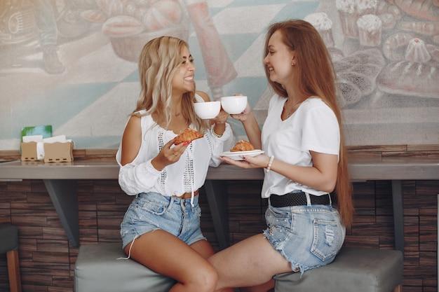 Mode jonge meisjes zitten in een café Gratis Foto
