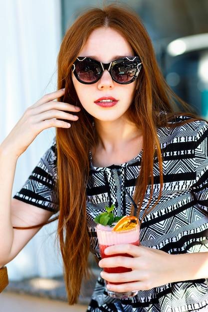 Mode jonge vrouw met lange haren en geweldige glimlach, met smakelijke zoete zomercocktaillimonade, elegante jurk en, make-up, ontspannen in het stadscafé. gelukkige vreugdevolle emoties. Gratis Foto