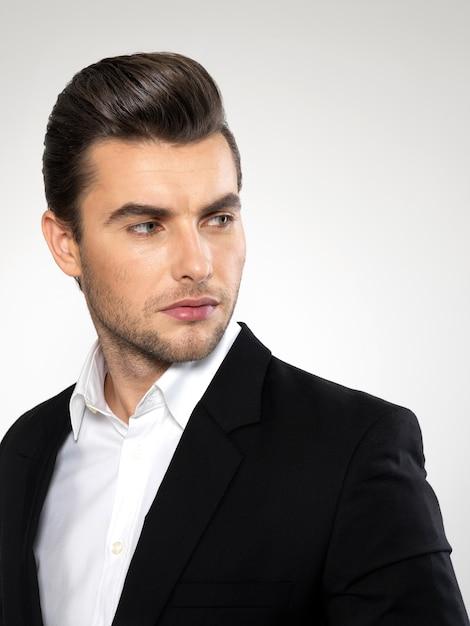 Mode jonge zakenman zwart pak casual poses in de studio Gratis Foto