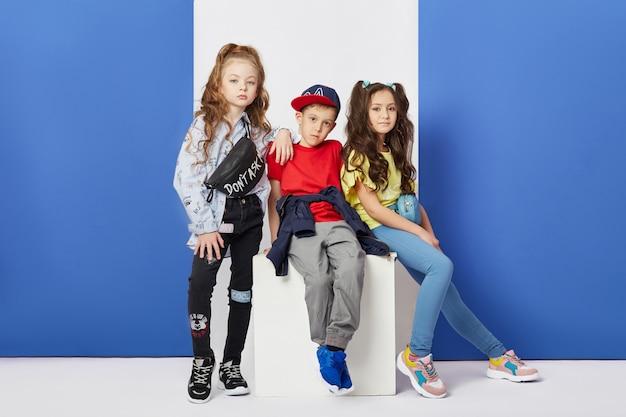 Mode jongen en meisje stijlvolle kleding gekleurde muur Premium Foto