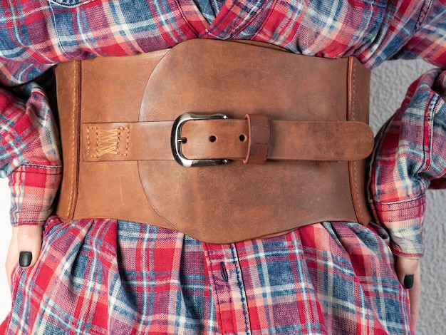 Mode. leren brede damesriem van bruine kleur met een gesp, gekleed voor een meisje in een rood shirt in een kooi Premium Foto