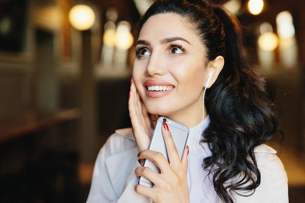 Mode levensstijl concept. portret van leuke vrouw met pony staart met charmante glimlach luisteren naar muziek Premium Foto