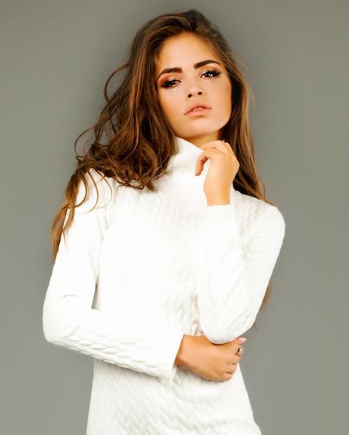 Mode levensstijl portret van jonge gelukkig mooie vrouw in witte jurk op grijze muur Gratis Foto