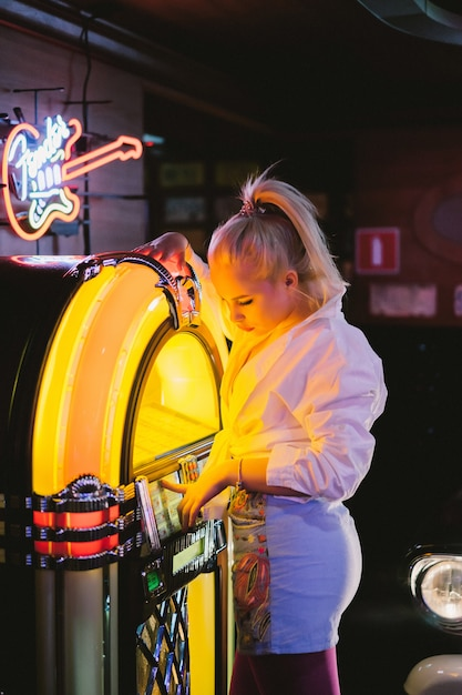 Mode meisje in een vintage café in de stijl van pin-up. Gratis Foto