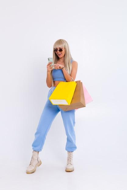 Mode portret van jonge blonde vrouw met lang prachtig steil haar houdt kleurrijke boodschappentassen Gratis Foto