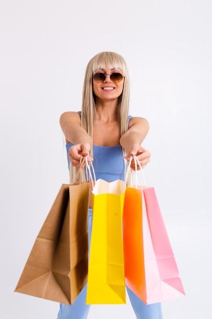 Mode portret van jonge blonde vrouw met prachtig lang steil haar met kleurrijke boodschappentassen in de studio op een wit. Gratis Foto