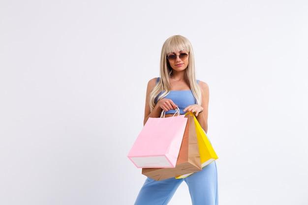 Mode portret van jonge blonde vrouw met prachtig lang steil haar met kleurrijke boodschappentassen Gratis Foto