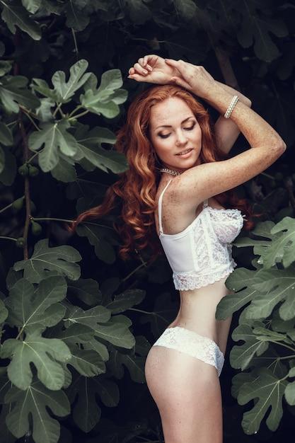 Mode portret van jonge mooie sexy vrouw met lang golvend rood haar. mooi meisje in witte beha of lingerie in de zomertuin. mode stijl afgezwakt kleuren portret. Premium Foto