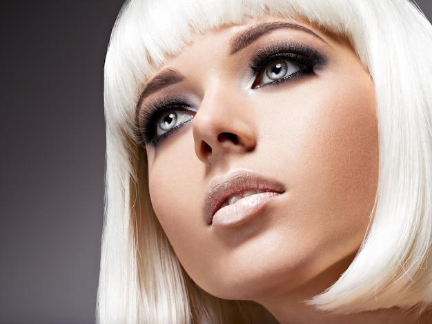 Mode portret van jonge mooie vrouw met witte haren en zwarte make-up van oog Gratis Foto