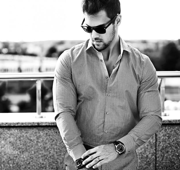 Mode portret van jonge sexy knappe model man in casual kleding in zonnebril in de straat Gratis Foto
