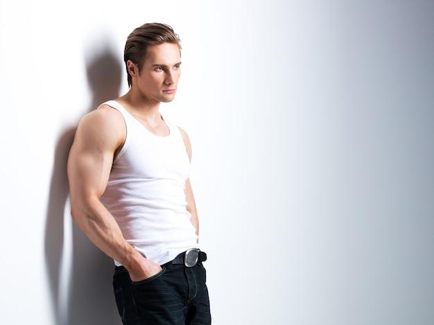 Mode portret van knappe jongeman in wit overhemd zijwaarts op zoek vormt over muur met contrast schaduwen. Gratis Foto