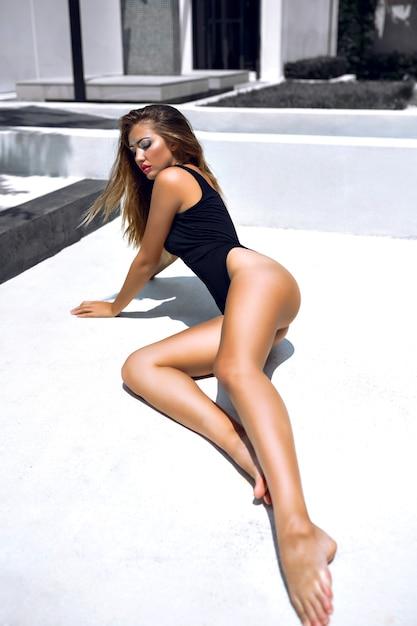 Mode portret van model met prachtig gebruind lichaam, creatieve kunst make-up, lag op de vloer, stijlvolle, minimalistische zwarte bikini dragen. Gratis Foto