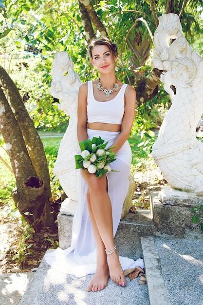 Mode portret van mooie creatieve bruid, met exotische lotus boeket, stijlvolle ongebruikelijke bruiloft outfit en grote diamanten halsketting. Gratis Foto