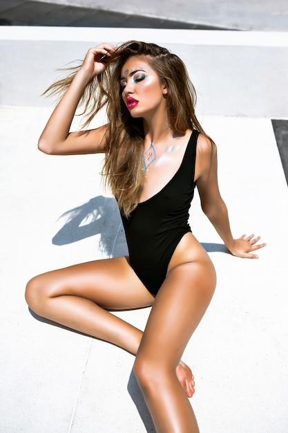 Mode portret van prachtige sexy vrouw met perfect gebruind lichaam, kunst creatieve make-up, op de grond zitten, zwarte bikini, minimalistische stijl, getinte kleuren. Gratis Foto