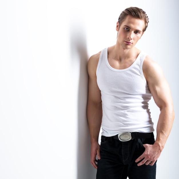 Mode portret van sexy jonge man in wit overhemd vormt over muur met contrast schaduwen. Gratis Foto