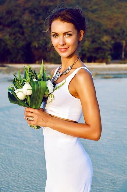 Mode portret van tedere stijlvolle bruid met eenvoudige moderne trouwjurk poseren met verbazingwekkende exotische witte lotus boeket op het strand. 's avonds gouden zonlicht. Gratis Foto