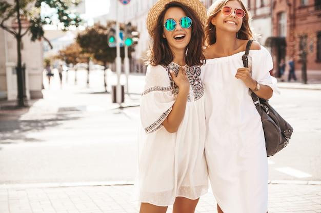 Mode portret van twee jonge stijlvolle hippie brunette en blonde vrouwen in zonnige zomerdag. modellen gekleed in witte hipster kleding. dames poseren. gek worden Gratis Foto