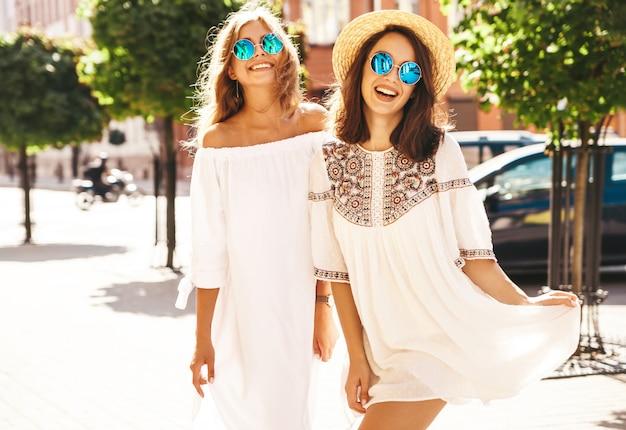 Mode portret van twee jonge stijlvolle hippie brunette en blonde vrouwen modellen in zonnige zomerdag in witte hipster kleding poseren. gek worden Gratis Foto