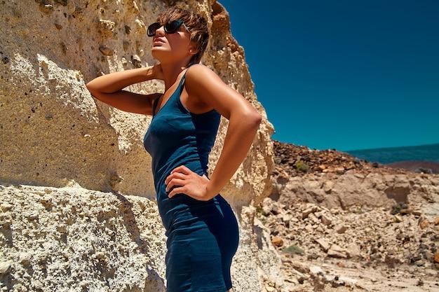 Mode stijlvolle mooie jonge brunette vrouw model in zomer blauwe jurk poseren in de buurt van zandrotsen Gratis Foto