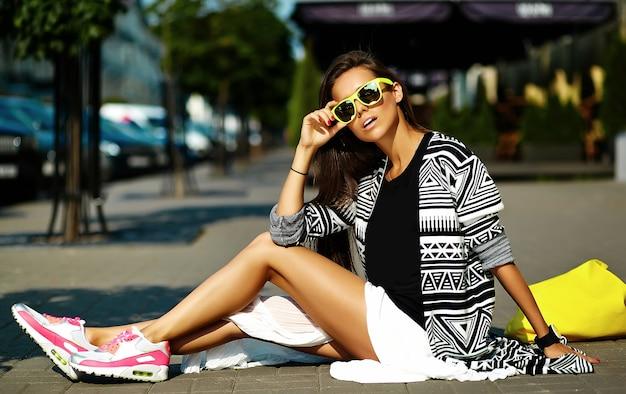 Mode stijlvolle mooie jonge brunette vrouw model in zomer hipster kleurrijke casual kleding die zich voordeed op straat achtergrond Gratis Foto