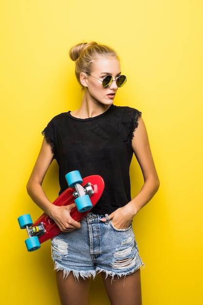 Mode vrij cool meisje in zonnebril met skateboard over kleurrijke gele achtergrond Gratis Foto