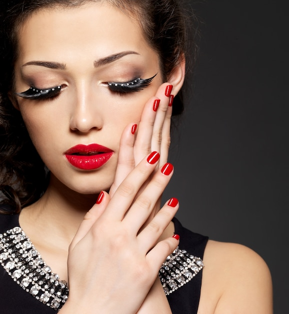 Mode vrouw met moderne creatieve make-up met behulp van valse wimpers rode manicure Gratis Foto