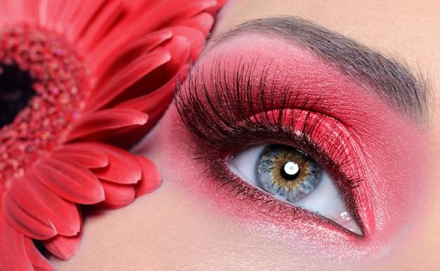 Mode vrouw oog met rode make-up en lange valse wimpers - bloem op de achtergrond Gratis Foto