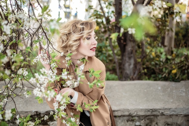 Mode vrouw portret van vrij trendy meisje poseren in de stad in europa, lente straatmode. lachend en lachend portret. retro stijl, regenjas en rode lippen Premium Foto