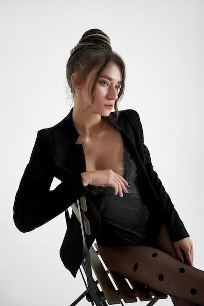 Mode vrouw zittend op een stoel op een wit, mooi slank lichaam van een vrouw Premium Foto