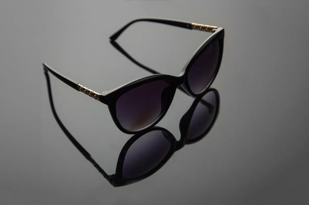 Mode vrouwen zonnebril, zwart plastic, gouden decoratie op de douche, stijlvolle gradiënt achtergrond met polarisatiefilter. Premium Foto