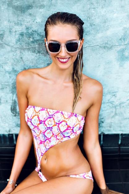 Mode zomerbeeld van sexy jonge vrouw, gekleed in heldere gedrukte bikini en vintage zonnebril, nat lichaam en haren, stedelijke muur, vakantiestijl. Gratis Foto