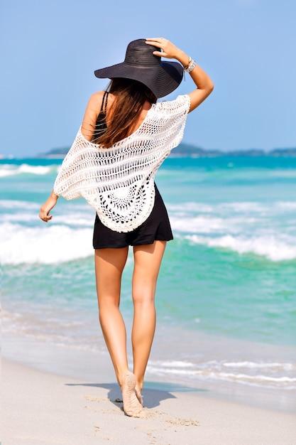 Mode zomerbeeld van vrouw poseren terug, in de buurt van blauwe zeewater, mooie zonnige zomerdag, ontspannen einde genieten van vrijheid, vreugde, geluk, heldere kleuren Gratis Foto