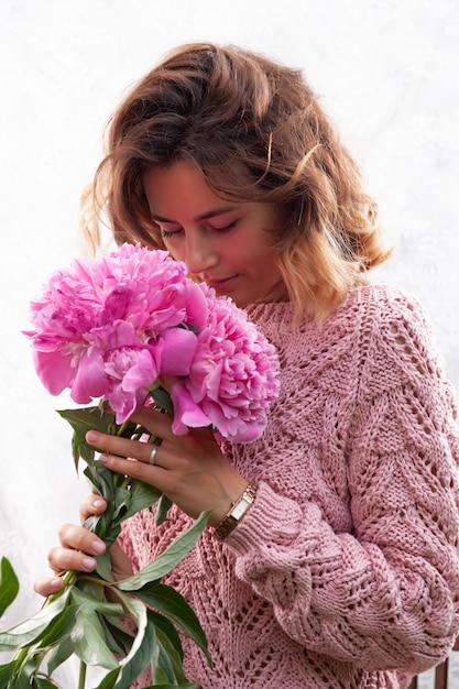 Model in bruine gebreide trui met natuurlijke make-up en roze pioenrozen Premium Foto