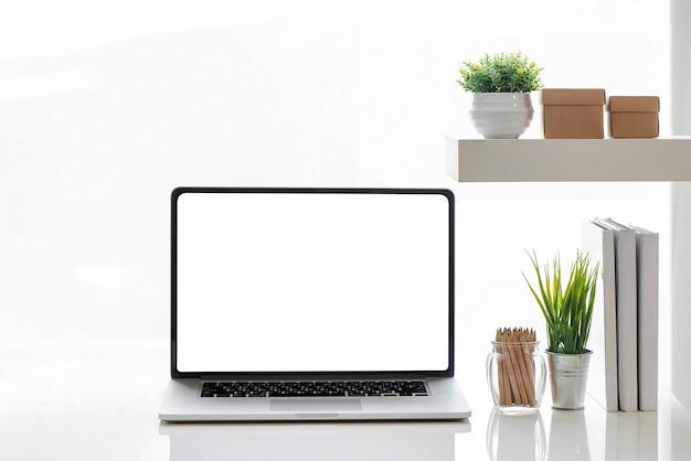 Model laptop met wit scherm en benodigdheden op witte tafel. Premium Foto