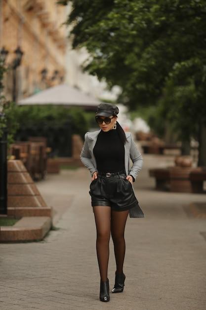Model meisje in zonnebril, lederen broek en trendy trenchcoat wandelen op de straat in de stad in de vroege herfst Premium Foto
