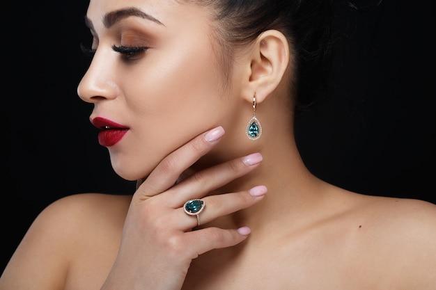 Model toont oorbellen en ring met prachtige blauwe edelstenen Gratis Foto