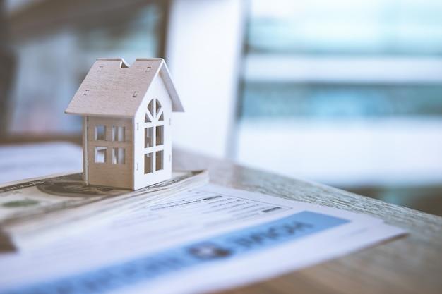 Model wit huis op dollarbankbiljet. verzekering en vastgoedbeleggingen onroerend goed concept. Premium Foto