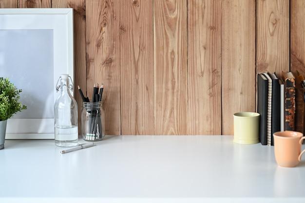 Modelaffiche op wit houten bureau met een mok en bureautoebehoren Premium Foto