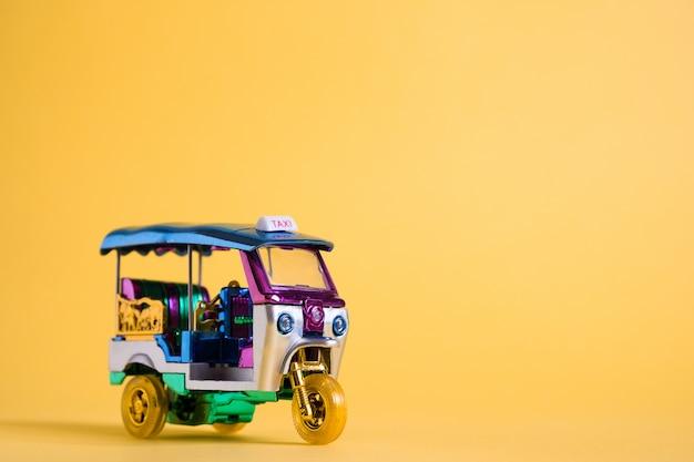 Modeldiestuk tuk tuk op gele muur wordt geïsoleerd. thaise traditionele taxi in bangkok thailand. souvenir Premium Foto