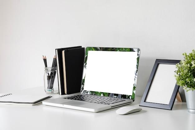 Modellaptop op werkruimte met fotokader, kruik potlood, muis op bureaulijst. Premium Foto