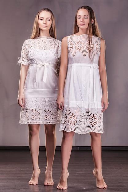 Modellen mooie vrouwelijke vriendinnen in zachte jurken met lang haar communiceren liefdevol met elkaar Premium Foto