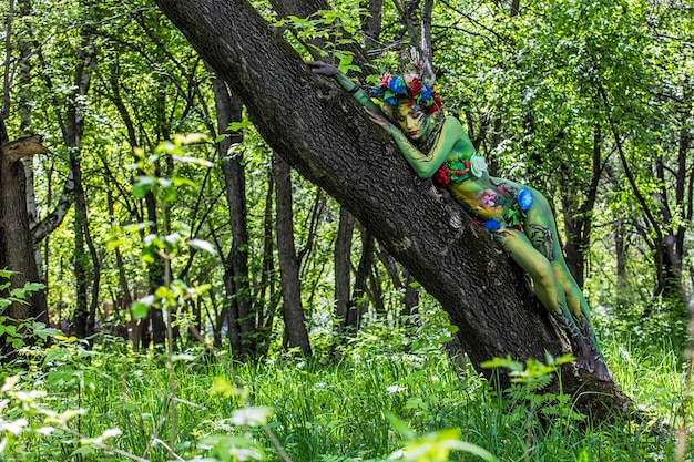 Modelvrouw in de vorm van een nimf tussen de bomen met ongebruikelijke mooie patronen op het lichaam Premium Foto