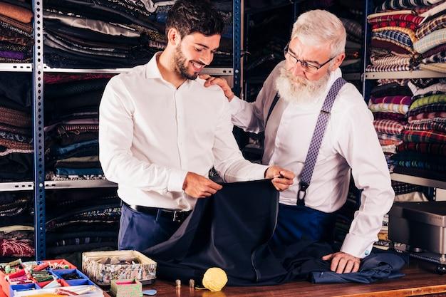 Modeontwerper en klant kijken naar stof in zijn winkel Gratis Foto