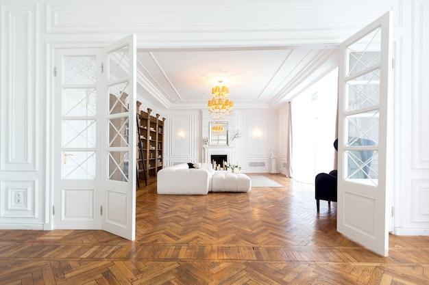 Modern interieur van een luxe groot licht tweekamerappartement. witte muren, luxe dure meubels, parketvloeren en witte binnendeuren Premium Foto