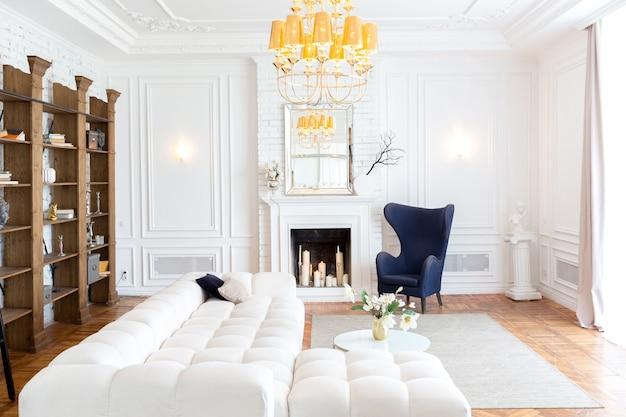 Modern interieur van een luxe grote lichte woonkamer. witte dure bank en houten planken, witte muren met lijstwerk en een luxe kroonluchter Premium Foto