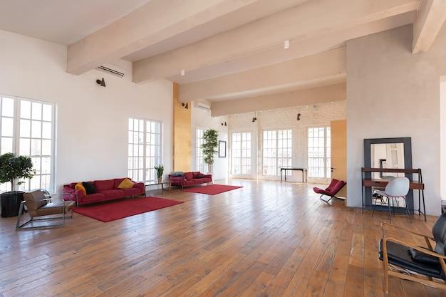 Modern ontwerp van een enorme witte lichte kamer met twee rode banken en veel grote ramen. vol zonneschijn. hoog plafond en houten parket Premium Foto